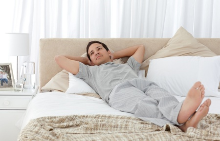 unbend: Tranquil man lying on his bed