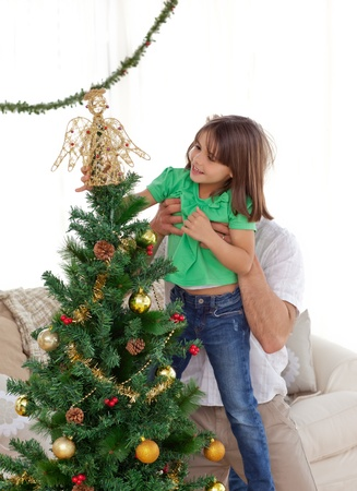 Attentive father holding her daughter to decorate the christmas tree photo