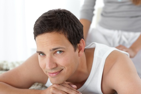 Portrait of a happy man being massaged by his girlfriend photo