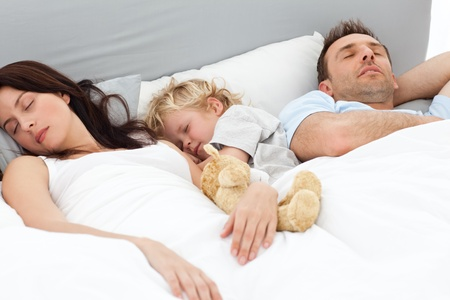 catnap: Relaxed little boy sleeping with his parents in their bed Stock Photo
