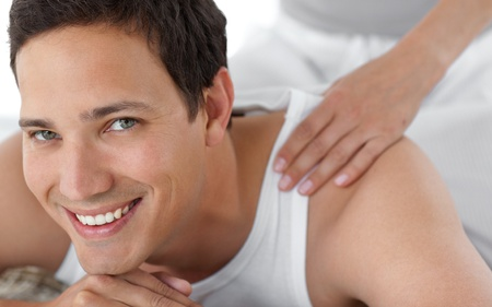 Portrait of a happy man receiving a massage from his girlfriend photo