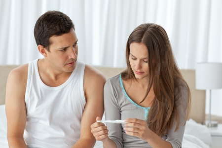 Worried couple looking at a pregnancy test sitting on their bed photo