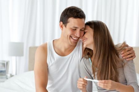 prueba de embarazo: Pareja alegre con una prueba de embarazo en el dormitorio Foto de archivo