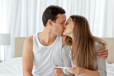 exam results: Couple kissing after looking at the result of a pregnancy test