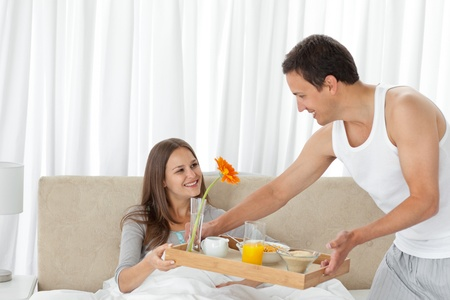 Attentive man serving the breakfast to his girlfriend on the bed photo