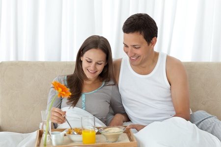 Young woman having breakfast on the bed with her boyfriend  Stock Photo - 10175303