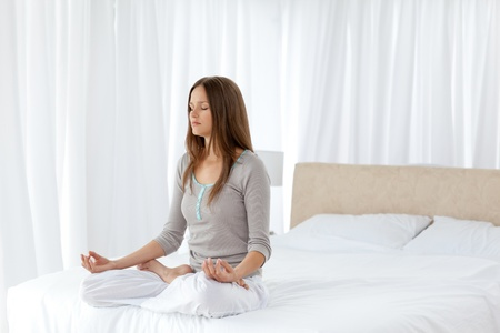 soften: Pretty woman doing yoga exercises sitting on her bed