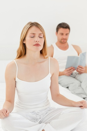 Woman practicing yoga while her husband is reading photo