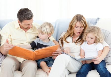 Family reading a book on their sofa photo