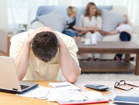 woman issues: Hombre calcular sus facturas mientras su familia est� en el sof� Foto de archivo