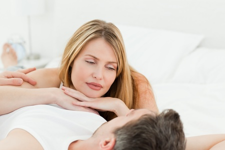 Lovely couple lying down together in their bed at home