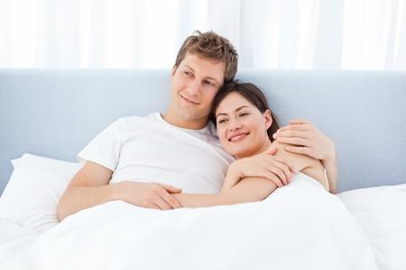 couple au lit: L'homme �treignant sa petite amie sur leur lit