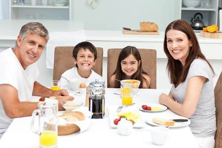 woman eat: Family having breakfast in the kitchen