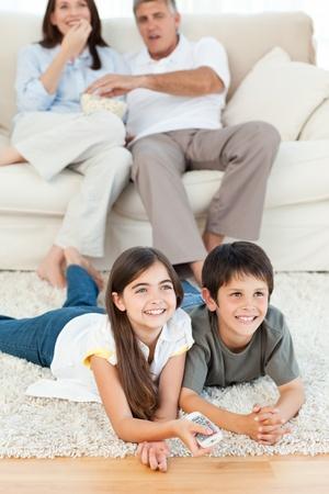 people watching tv: Familia viendo tv en la sala de estar