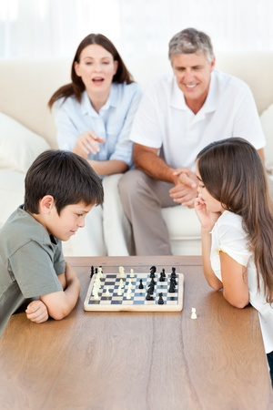 Parents looking their children playing chess Stock Photo - 10171718