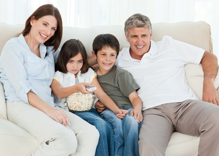 Family watching tv while they are eating popcorn photo