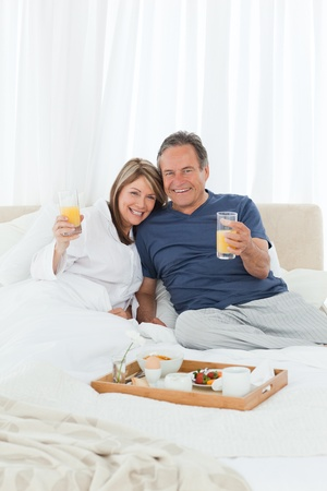 Lovely couple  having breakfast in their bed at home Stock Photo - 10172048