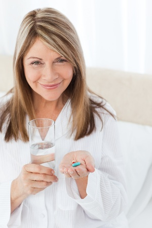 Sick woman taking her pills at home photo