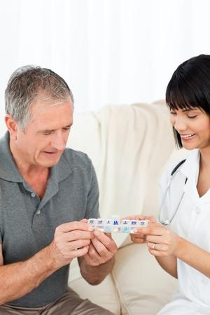 enfermera con paciente: Enfermera mostrando p�ldoras a su paciente