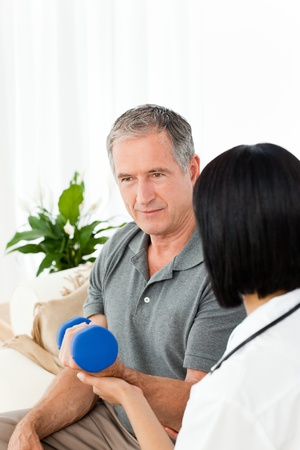 Nurse helping her patient to do exercises at home Stock Photo - 10174454