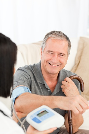 home health care: Retired man with his nurse at home Stock Photo