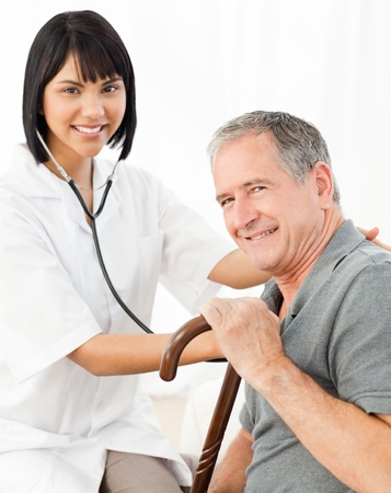 old carer: Senior laughing with his nurse at home