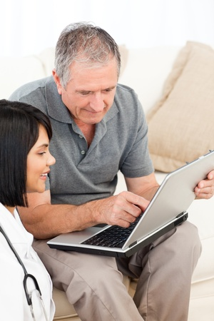 Mature man with his nurse looking at the laptop at home photo