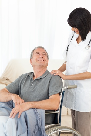 Man in his wheelchair with his nurse at home Stock Photo - 10172825