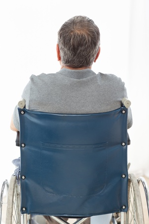 Mature man in his wheelchair with his back to the camera at home photo
