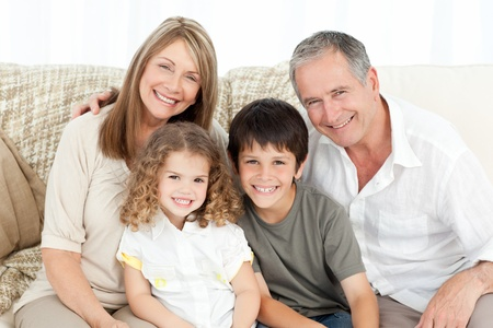 A happy family on their sofa looking at the camera at home photo