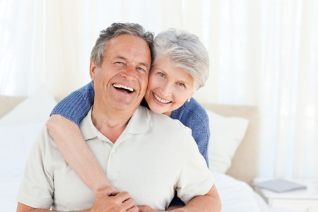 close together: Senior couple looking at the camera  at home