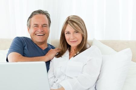 senior ordinateur: Couple en regardant la cam�ra � la maison
