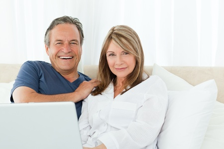 woman laptop happy: Couple looking at the camera at home