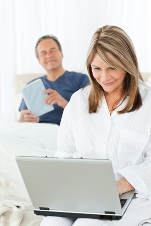 woman looking at his laptop while her  husband is reading at home photo
