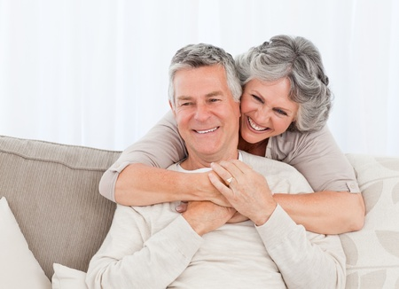 old man smiling: Mature woman hugging her husband at home Stock Photo