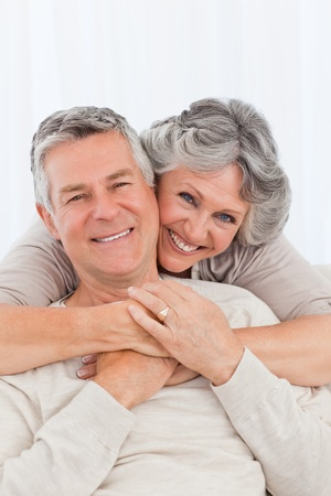 home health care: Mature woman hugging her husband at home Stock Photo