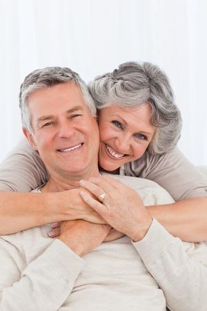 property insurance: Mujer madura abrazando a su marido en su casa