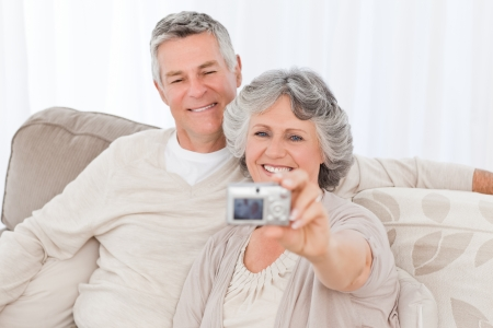 taking a wife: Mature couple taking a photo of themselves at home Stock Photo