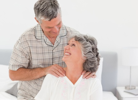 Retired woman giving a massage to her husband at home photo