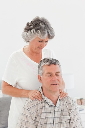 Retired woman giving a massage to her husband at home Stock Photo - 10173561