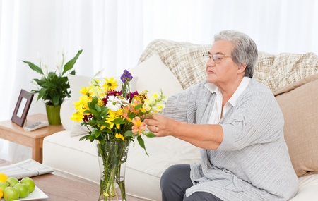 Senior with flowers  at home Stock Photo - 10169820