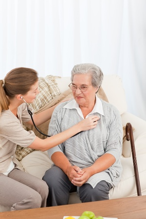 Nurse talking with her patient at home photo