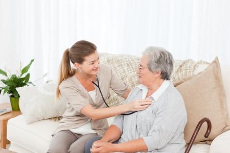 visits: Enfermera tomando el ritmo card�aco de su paciente en casa Foto de archivo