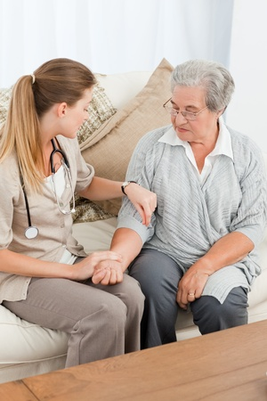 home care: Beautiful nurse taking the pulse of her patient at home Stock Photo
