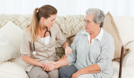 Lovely nurse helping her patient to do exercises at home Stock Photo - 10174787