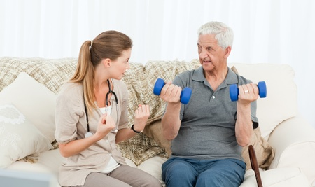old carer: Lovely nurse helping her patient to do exercises at home Stock Photo