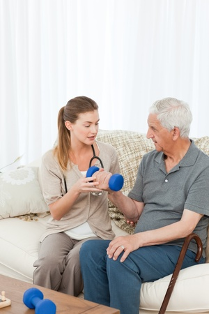 home visit: Lovely nurse helping her patient to do exercises at home Stock Photo