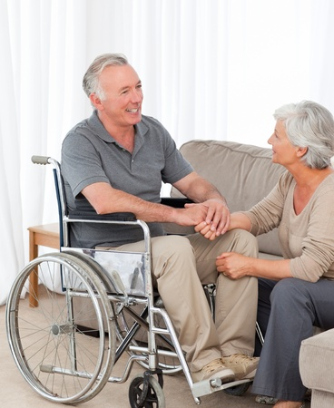 paralysis: Woman with her husband in a wheelchair