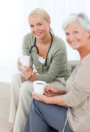 Doctor drinking with her patient Stock Photo - 10171275