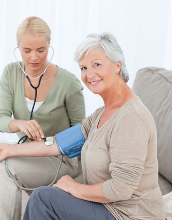 home health care: Lovely doctor taking the blood pressure of her patient